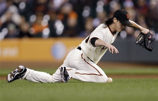 San Francisco Giants starting pitcher Tim Lincecum slides as he fields a ground ball from Arizona Diamondbacks' Justin Upton during the first inning of a baseball game Tuesday, Sept. 25, 2012, in San Francisco. Upton reached first base with an infield single on the play. (AP Photo/Marcio Jose Sanchez)