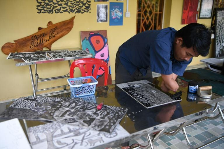 Morn Chear works with an arts collective based in Siem Reap, where he specialises in Linocut block printing -- a technique rarely used in Cambodia (AFP Photo/TANG CHHIN Sothy)