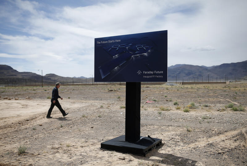 FILE - In this April 13, 2016, file photo, a man walks by a sign at an event to mark the start of construction for Faraday Future in North Las Vegas, Nev. Electric car maker Faraday Future said Monday, July 10, 2017 that it is deserting its plan to construct a $1 billion manufacturing plant in southern Nevada eight months after suspending the project and sinking at least $120 million into it. (AP Photo/John Locher, File)