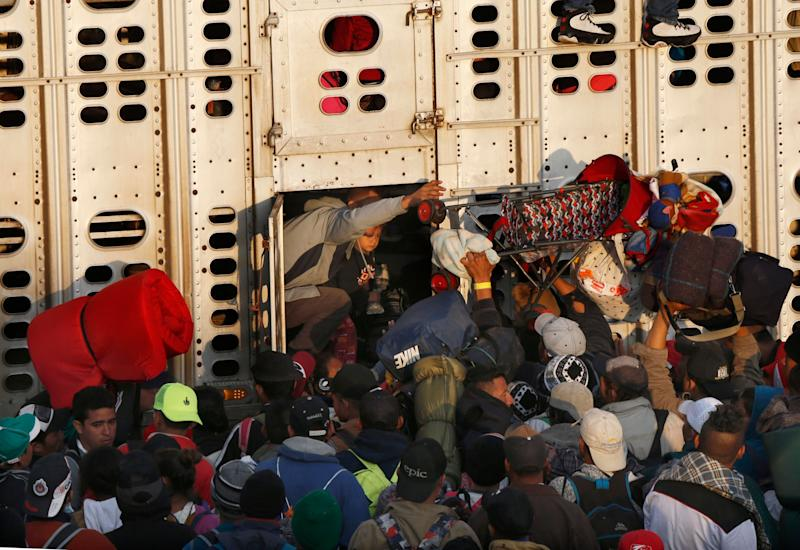 Central American migrants, part of the caravan hoping to reach the U.S. border, get a ride in a chicken truck, in Irapuato, Mexico, on Nov. 12, 2018. Several thousand Central American migrants marked a month on the road Monday as they hitched rides toward the western Mexico city of Guadalajara. (Photo: ASSOCIATED PRESS)