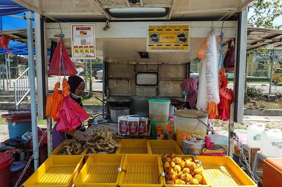 A petty trader sells fried snacks at her stall in Petaling Jaya October 27, 2020. — Picture by Miera Zulyana
