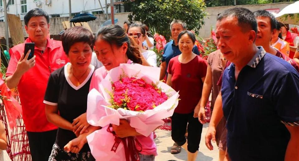 Chinese woman Jin Ting, carrying a bunch of flowers, reunited with her parents after 30 years. She went missing at the age of three.