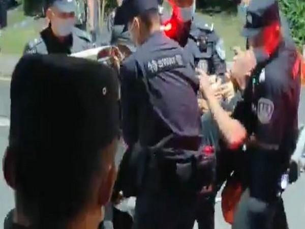 A protester being violently arrested by Chinese police.