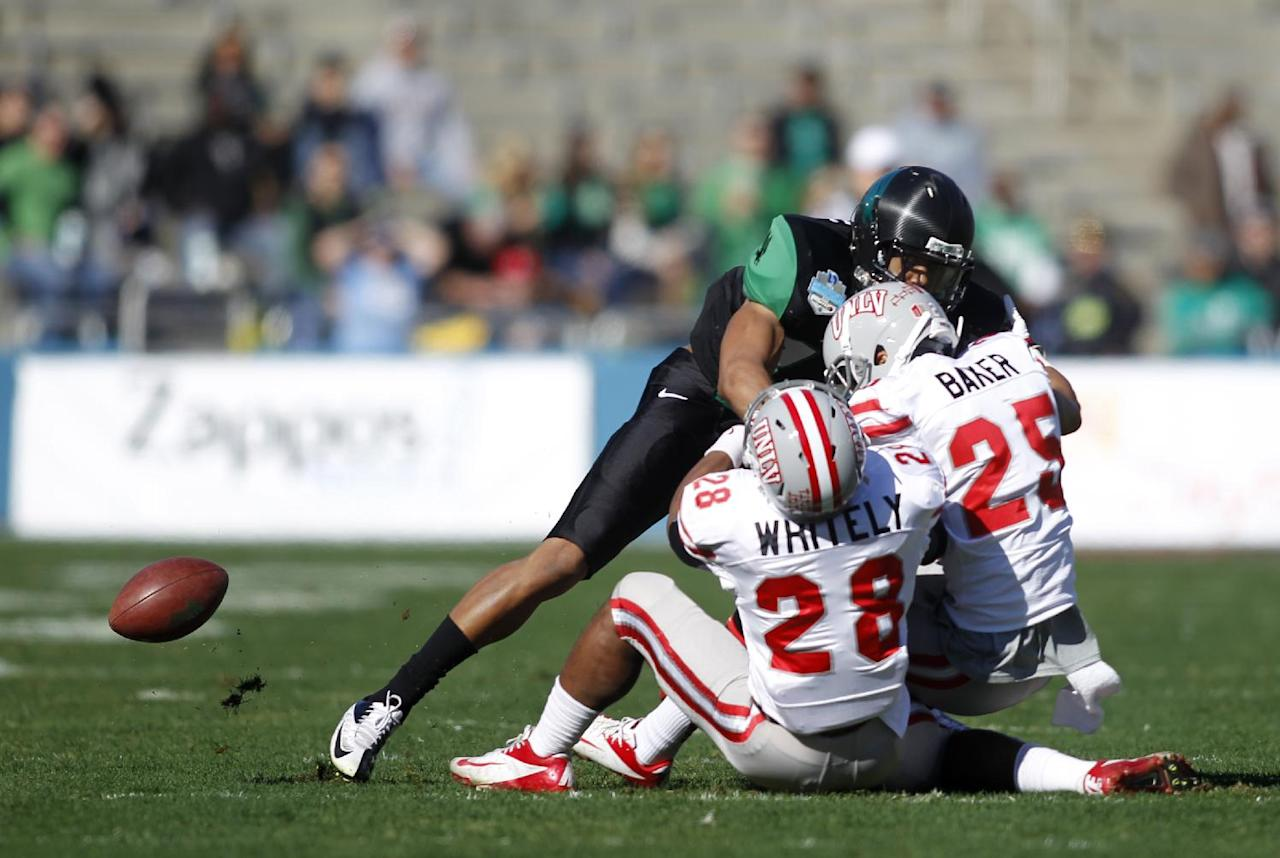 UNLV punt returner Keith Whitely (28) fumbles the ball as North Texas linebacker Jamal Marshall knocks defensive back Brandon Baker (25) into Whitely during the first half of the Heart of Dallas NCAA college football game, Wednesday, Jan. 1, 2014, in Dallas. (AP Photo/Mike Stone)