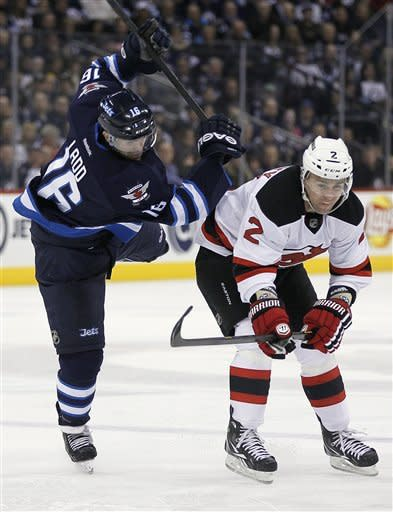 New Jersey Devils' Marek Zidlicky (2) checks Winnipeg Jets' Andrew Ladd (16) during the second period of an NHL hockey game in Winnipeg, Manitoba, on Thursday, Feb. 28, 2013. (AP Photo/The Canadian Press, John Woods)