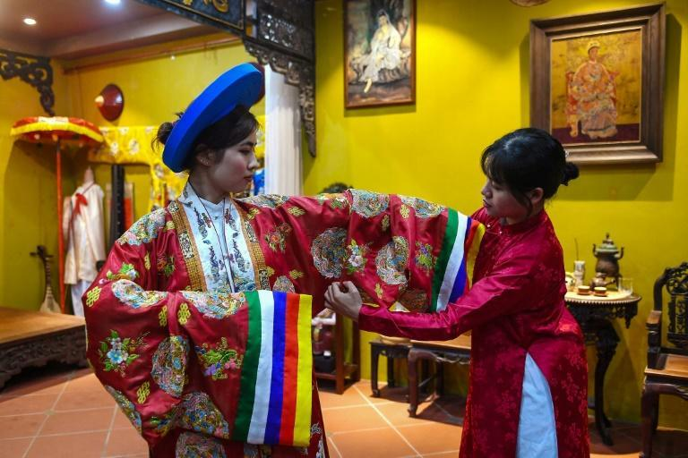 Student Pham Trang Nhung (L) tries on a traditional outfit in Hanoi