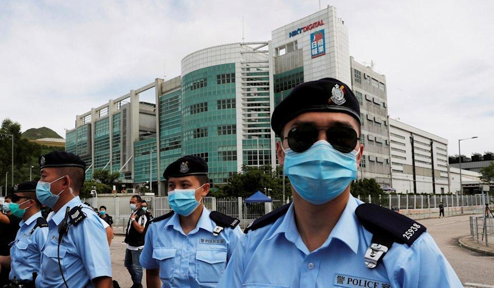 Police officers stand guard outside the headquarters of Apple Daily and Next Media after Jimmy Lai was detained by the national security unit in August last year. Photo: Reuters