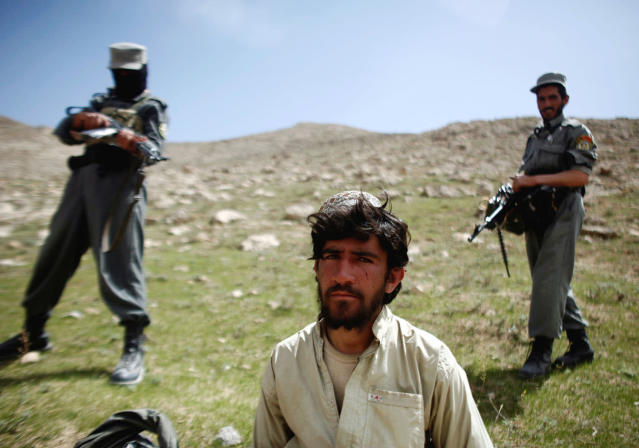 <p>Afghan policemen stand next to a captured Taliban fighter after a gun battle near the village of Shajoy in Zabol province March 22, 2008. (Photo: Goran Tomasevic/Reuters) </p>