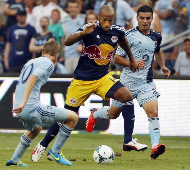 New York Red Bulls forward Thierry Henry (14) splits Sporting Kansas City midfielder Oriol Rosell (20) and forward Soony Saad, right, during the first half of an MLS soccer match in Kansas City, Kan., Saturday, Aug. 3, 2013. (AP Photo/Orlin Wagner)