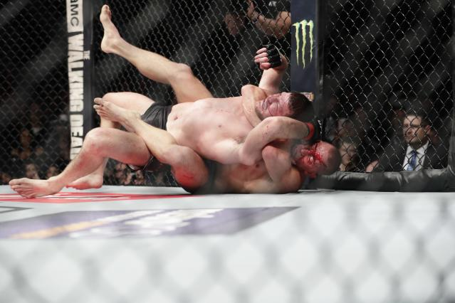 Georges St-Pierre, below, of Canada, fights England's Michael Bisping during a middleweight title mixed martial arts bout at UFC 217 early Sunday, Nov. 5, 2017, in New York. St-Pierre won the fight. (AP Photo/Frank Franklin II)