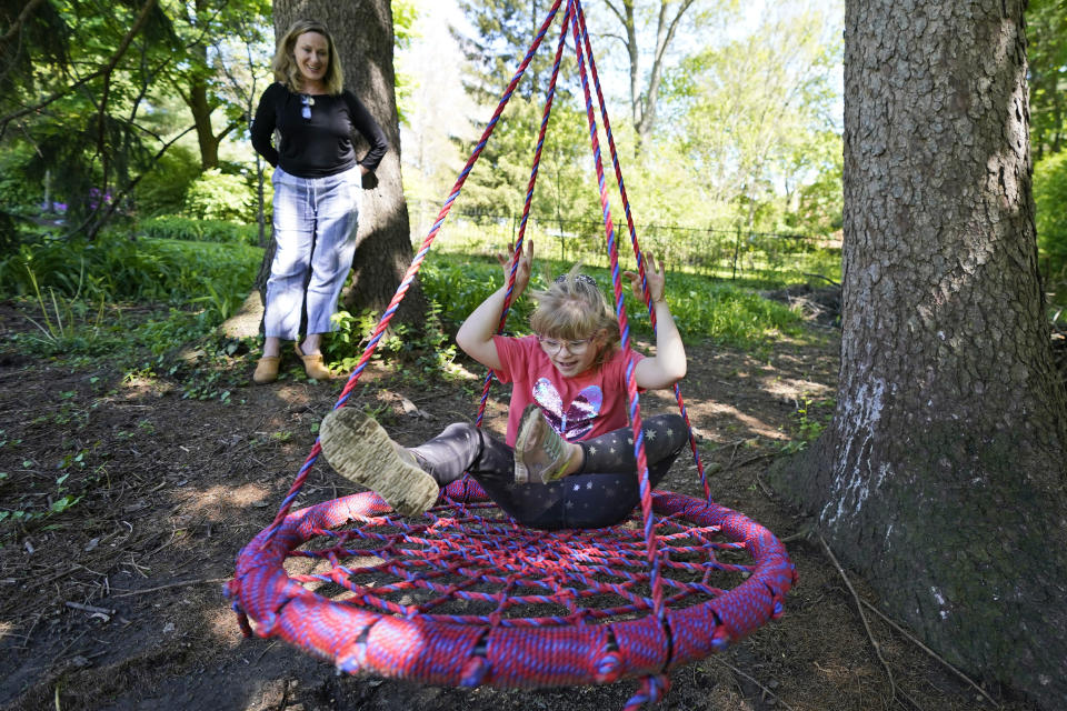Holly Christensen, left, watches her daughter, Lyra, twirl in a swing, Thursday, May 13, 2021, in Akron, Ohio. Anti-abortion activists say 2021 has been a breakthrough year for legislation in several states seeking to prohibit abortions based on a prenatal diagnosis of Down syndrome. Opponents of the bills, including some parents with children who have Down syndrome like Holly, argue that elected officials should not be meddling with a woman's deeply personal decision on whether to carry a pregnancy to term after a Down syndrome diagnosis. (AP Photo/Tony Dejak)