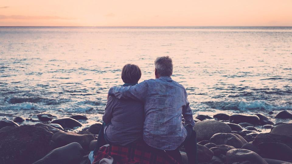 love and romance with adult  matures - elderly couple sitting and hugging each other looking at the sea at sunset relaxing.