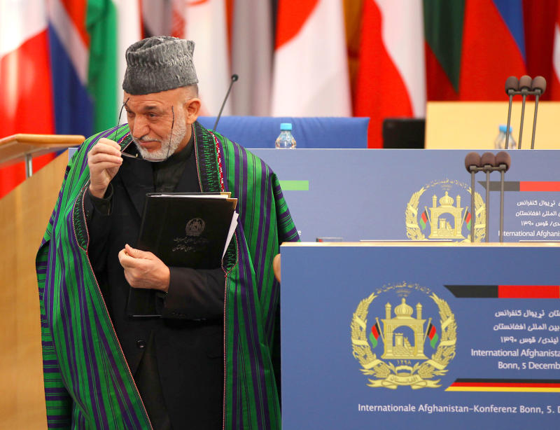 The President of Afghanistan, Hamid Karzai,  leaves after he delivered  his speech at the International Afghanistan Conference in Bonn, Germany Monday Dec. 5, 2011.  A decade after the first Afghanistan conference the international community discusses the future of its engagement in Afghanistan. (AP Photo/Oliver Berg, Pool)