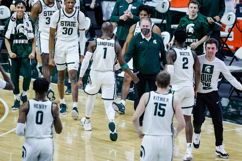 Michigan State guard Joshua Langford (1) high-fives coach Tom Izzo after scoring a basket to force Illinois into calling timeout during the first half at Breslin Center in East Lansing, Tuesday, Feb. 23, 2021.