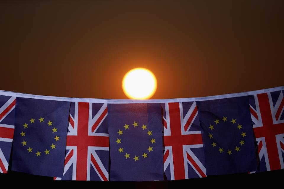 KNUTSFORD, UNITED KINGDOM - MARCH 17:  In this photo illustration, the sun sets behind European Union and the Union flag bunting on March 17, 2016 in Knutsford, United Kingdom. The United Kingdom will hold a referendum on June 23, 2016 to decide whether or not to remain a member of the European Union (EU), an economic and political partnership involving 28 European countries which allows members to trade together in a single market and free movement across its borders for citizens.  (Photo illustration by Christopher Furlong/Getty Images)