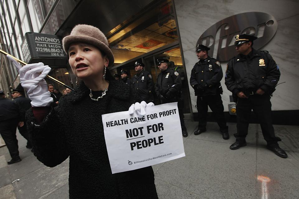 "NEW YORK, NY - FEBRUARY 29: A protester stands as NYPD guard an entrance at Pfizer headquarters during an Occupy Wall Street ""Shut Down the Corporations"" protest on February 29, 2012 in New York City. Occupy movements across the country are planning protests in dozens of cities against corporate power. (Photo by Mario Tama/Getty Images)"