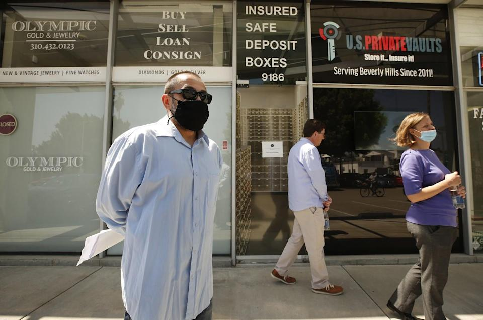 A masked man holding papers stands outside a store