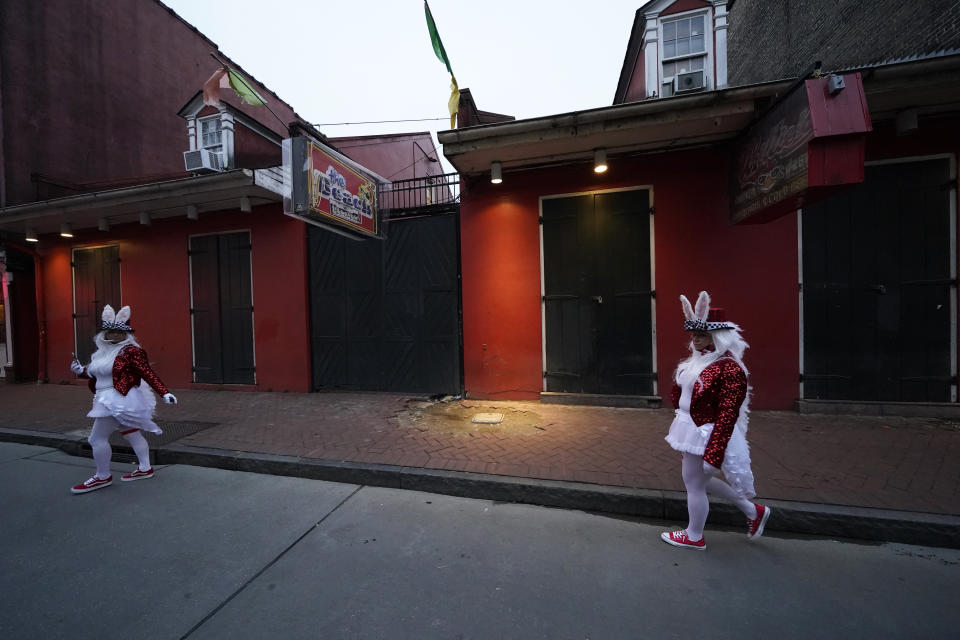 People in costume walk past a shuttered bar on Bourbon Street in the French Quarter of New Orleans, Friday, Feb. 12, 2021. New Orleans' annual pre-Lenten Mardi Gras celebration is muted this year because of the coronavirus pandemic. Parades canceled. Bars closed. Crowds suppressed. Mardi Gras joy is muted this year in New Orleans as authorities seek to stifle the coronavirus's spread. And it's a blow to the tradition-bound city's party-loving soul. (AP Photo/Gerald Herbert)