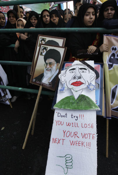 Iranian demonstrators, one holding a caricature of President Barack Obama next to a poster of Iranian Supreme Leader Ayatollah Ali Khamenei, attend an annual state-backed rally in front of the former US Embassy in Tehran, Iran, Friday, Nov. 2, 2012. The rally marks the Nov. 4, 1979, storming of the building by militant students who held 52 Americans hostage for 444 days to protest U.S. failure to hand over the toppled shah Mohammad Reza Pahlavi to Iran for trial. Gen. Mohammad Reza Naqdi of the powerful Revolutionary Guard, not shown, addressed the rally saying the U.S. must annul the CIA, pull out its warships from the Persian Gulf and dismantle its military bases from 50 countries around the world if it wants to restore ties with Tehran. (AP Photo/Vahid Salemi)