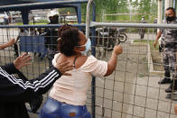 A relative of an inmate grabs a fence outside the Centro de Privación de Libertad Zona 8 prison where riots broke out in Guayaquil, Ecuador, Tuesday, Feb. 23, 2021. Deadly riots broke out in prisons in three cities across the country due to fights between rival gangs, according to police. (AP Photo/Angel Dejesus)