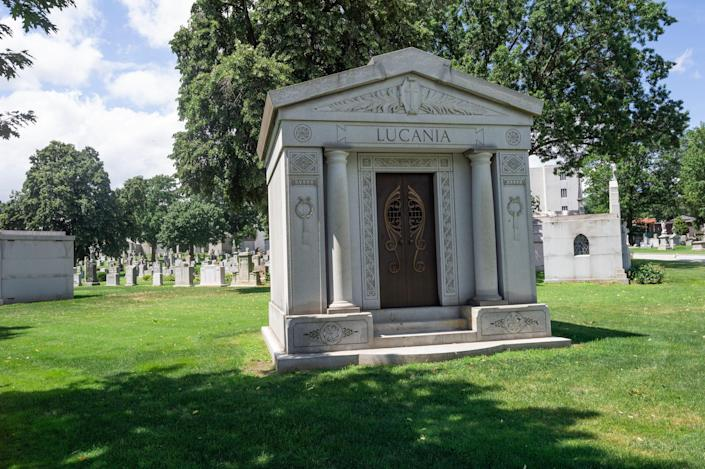 A small mausoleum is seen in a grassy cemetery, with smaller grave stones in behind it.