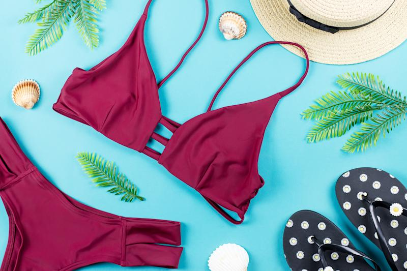 Summer holiday background. Tropical summer concept with red bikini, leaves and seashells on blue background. Flat lay, top view