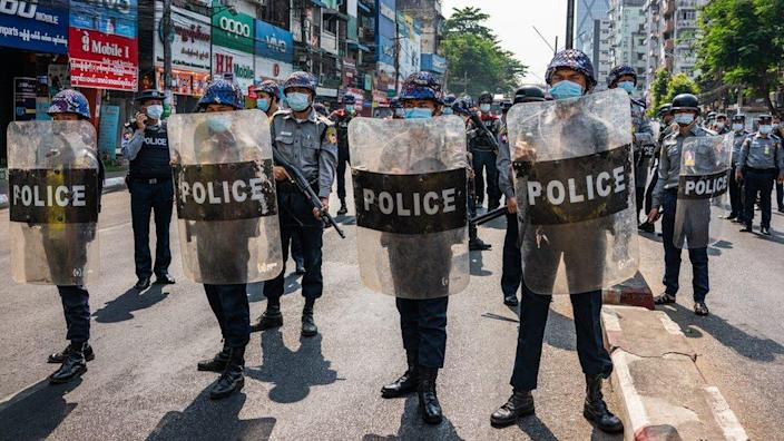 Riot police stand guard as anti-coup protesters march through the streets in Yangon, Myanmar