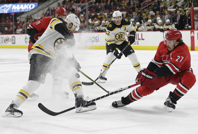 Boston Bruins' Rick Nash and Carolina Hurricanes' Justin Faulk (27) chase the puck during the first period of an NHL hockey game in Raleigh, N.C., Tuesday, March 13, 2018. (AP Photo/Gerry Broome)