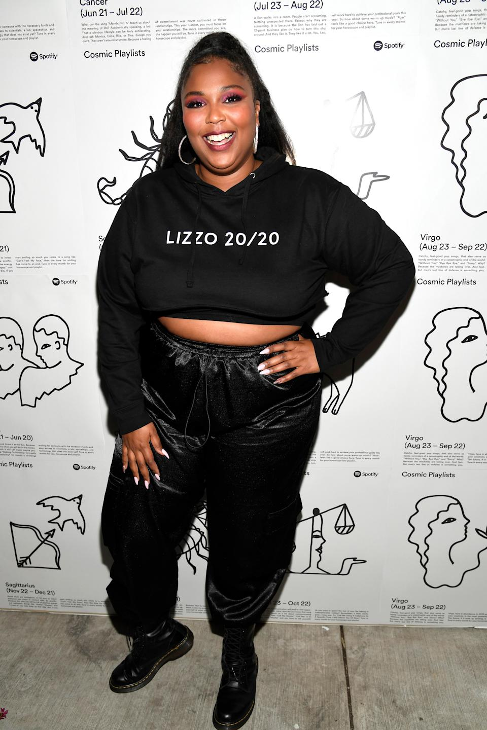 """Lizzo proved once again that she is her biggest cheerleader when she kept it cute and casual in a black """"Lizzo 20/20"""" sweater crop top and baggy black trousers."""