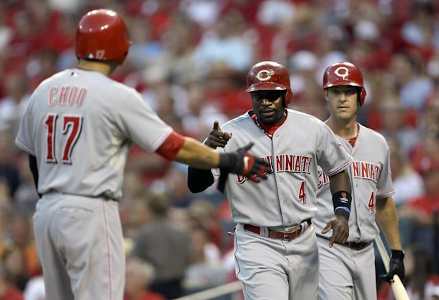 Cincinnati Reds' Brandon Phillips, center, and Shin-Soo Choo, left, celebrate as Ryan Ludwick, right, watches after scoring on a two-run single by Jay Bruce during the first inning of a baseball game against the St. Louis Cardinals, Wednesday, Aug. 28, 2013, in St. Louis. (AP Photo/Jeff Roberson)