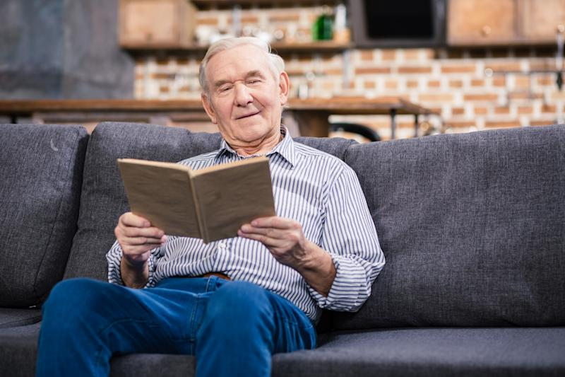 Older man sitting on a couch, reading a book