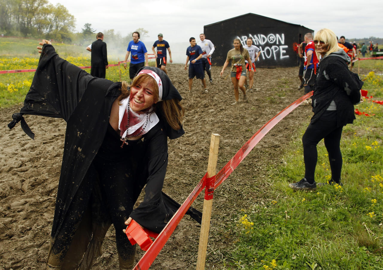 "A zombie in nun's clothing chases runners on the ""Run for Your Lives"" 5K obstacle course race in Amesbury, Massachusetts May 5, 2012.  Runners face man-made and natural obstacles on the course, while being chased by zombies, who try to take ""health"" flags off the runners belts.   REUTERS/Brian Snyder"