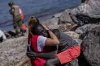 A migrant is comforted by a member of the Spanish Red Cross near the border of Morocco and Spain, at the Spanish enclave of Ceuta, on Tuesday, May 18, 2021. (AP Photo/Bernat Armangue)