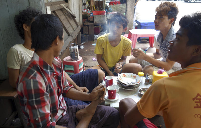 In this Aug. 4, 2013 photo, Myanmar men sit around a table and smoke as they chat at a roadside teashop in Yangon, Myanmar. As some of the world's biggest companies trumpet their arrival in Asia's hottest frontier market, the tobacco industry has a different strategy: It's slipping into Myanmar without fanfare. In this impoverished nation of 60 million people emerging from a half-century of isolation and brutal military rule two years ago, awareness about the health hazards is low, tobacco controls are weakly enforced, and the anti-smoking lobby is effectively a one man act. (AP Photo/Khin Maung Win)