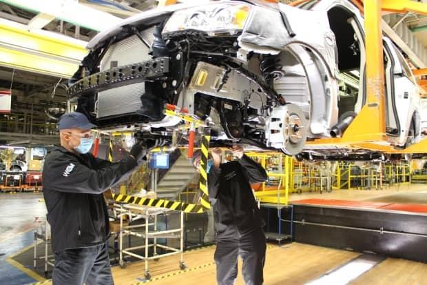 After a general lockdown in March, the economy bounced back in part due to strong manufacturing growth. Pictured here, two operators working on the underbody of a Dodge Grand Caravan at a Windsor Assembly Plant in Windsor, Ont., in May 2020.