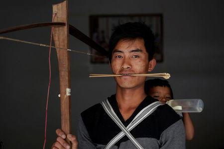 Zhang, a 26-year old ethnic Lisu man carries his daughter as he poses for a photograph with a crossbow at his house in Luzhang township of Nujiang Lisu Autonomous Prefecture in Yunnan province, China, March 26, 2018. REUTERS/Aly Song