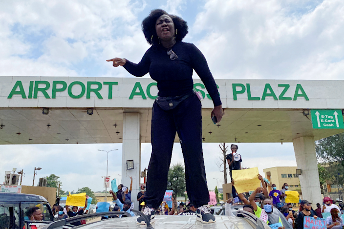 A demonstrator stands atop a vehicle and shouts slogans as others carry banners while blocking a road leading to the airport, during a protest over alleged police brutality, in Lagos, Nigeria - 12 October 2020