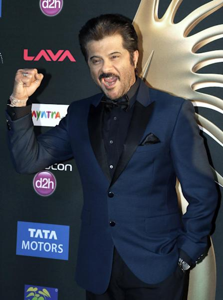 Indian film star Anil Kapoor gestures as he poses for photographers along the green carpet as he arrives for 15th annual International Indian Film Awards Saturday, April 26, 2014, in Tampa, Fla. (AP Photo/Chris O'Meara)