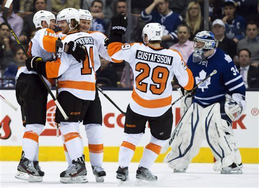 Philadelphia Flyers forward Jay Rosehill, back center, celebrates his goal with teammates as Toronto Maple Leafs goalie James Reimer, right, looks on during the second period of an NHL hockey game in Toronto on Thursday, April 4, 2013. (AP Photo/The Canadian Press, Nathan Denette)