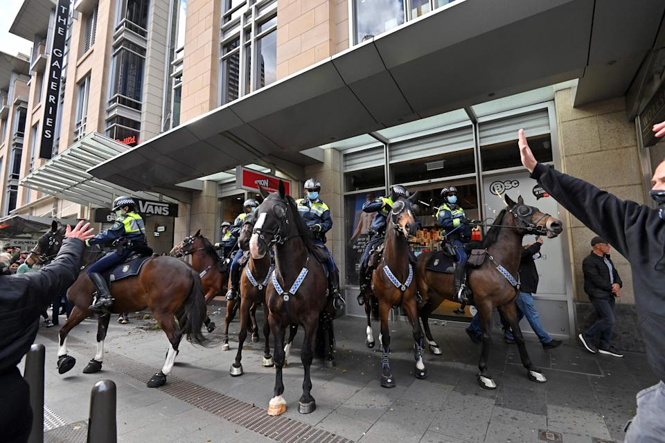 Police officers on horseback disperse protesters during a rally in Sydney on July 24, 2021, as thousands of people gathered to demonstrate against the city's month-long stay-at-home orders. (Photo by Steven SAPHORE / AFP) (Photo by STEVEN SAPHORE/AFP via Getty Images)