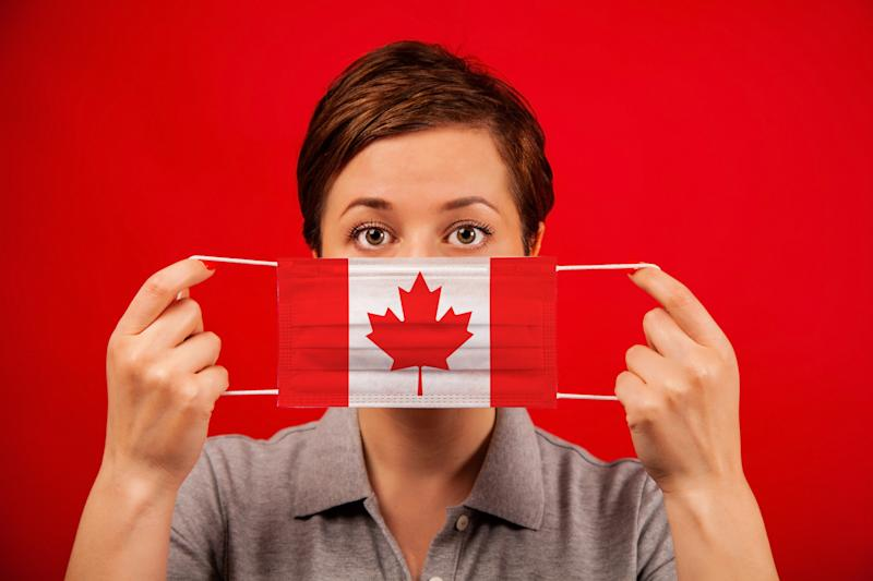 Coronavirus COVID-19 in Canada. Woman in medical protective mask with the image of the flag of Canada. The concept of preventing the spread of the epidemic and treating coronavirus.