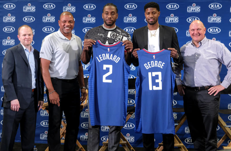 Kawhi Leonard, center, and Paul George , second right, holding their new team jerseys, pose with Los Angeles Clippers President of Basketball Operations Lawrence Frank, left, head coach Doc Rivers, second left, and team chairman Steve Ballmer during a press conference in Los Angeles, Wednesday, July 24, 2019. Nearly three weeks after the native Southern California superstars shook up the NBA by teaming up with the Los Angeles Clippers, the dynamic duo makes its first public appearance. (AP Photo/Ringo H.W. Chiu)