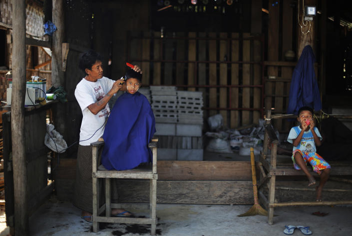 In this Feb. 11, 2014 photo, a Myanmarese barber trims the hair of a boy in Ma Kyone Galet village, inhabited by Moken and Myanmarese fishermen, on Bocho Island in Mergui Archipelago, Myanmar. The village, located within the Lampi National Park, is home to 480 Burmese and other ethnic groups, 280 Moken and 146 from Moken-Burmese marriages, as of a 2012 count. Isolated for decades by the country's former military regime and piracy, the Mergui archipelago is thought by scientists to harbor some of the world's most important marine biodiversity and looms as a lodestone for those eager to experience one of Asia's last tourism frontiers before, as many fear, it succumbs to the ravages that have befallen many of the continent's once pristine seascapes. (AP Photo/Altaf Qadri)