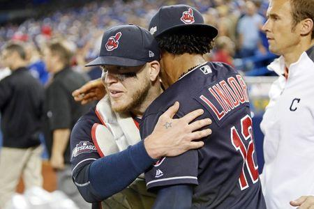 Cleveland Indians catcher Roberto Perez (55) and shortstop Francisco Lindor (12) celebrate after beating the Toronto Blue Jays in game five of the 2016 ALCS playoff baseball series at Rogers Centre. Mandatory Credit: John E. Sokolowski-USA TODAY Sports