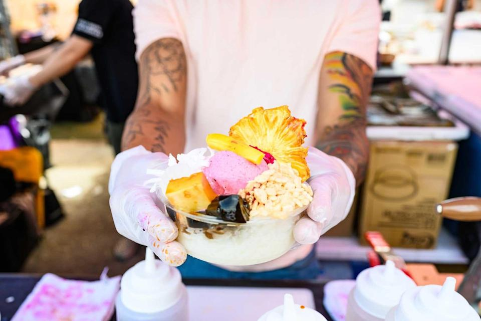 In New York City, United States a working food vendor wearing protective gloves shows a freshly made Philippine dessert at the Smorgasburg food event.