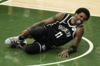 Brooklyn Nets' Kyrie Irving holds his leg after being injured during the first half of Game 4 of the NBA Eastern Conference basketball semifinals game against the Milwaukee Bucks Sunday, June 13, 2021, in Milwaukee. (AP Photo/Morry Gash)