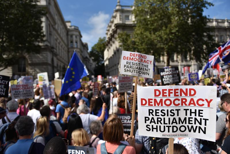 "LONDON, ENGLAND - AUGUST 31: Protesters hold placards saying ""Defend Democracy resist the parliament shutdown"" outside the gates of Downing Street on August 31, 2019 in London, United Kingdom.Left-wing group Momentum and the People's Assembly are coordinating a series of ""Stop The Coup"" protests across the UK aimed at Boris Johnson and the UK government proroguing Parliament. (Photo by John Keeble/Getty Images)"