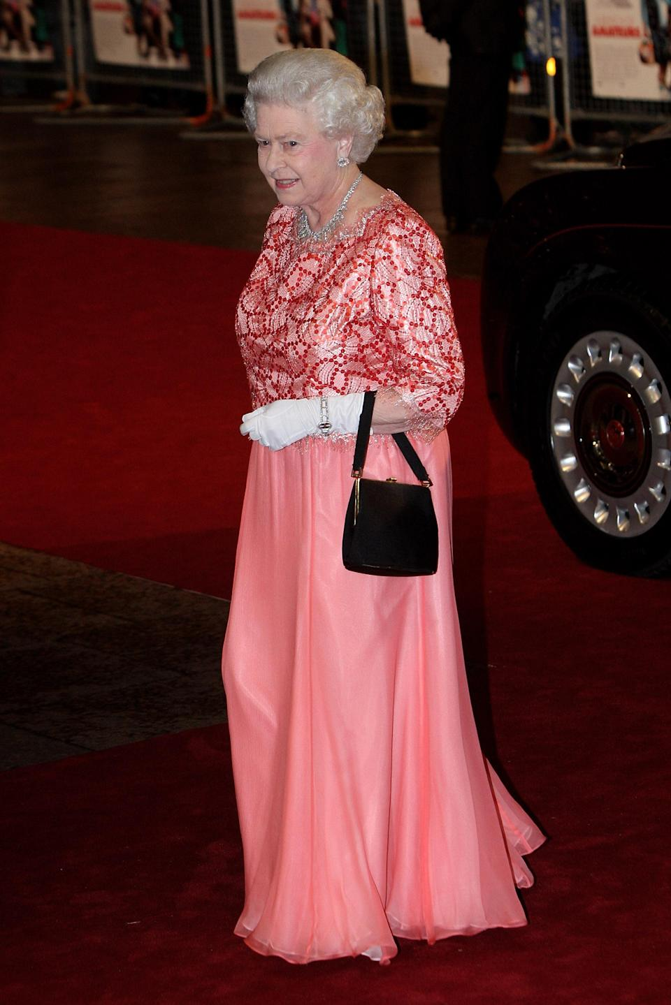 <p>Before the fash pack knew millennial pink was soon to be the 'It' hue of the moment, the Queen chose the colour for the red carpet – miniature handbag in tow. <em>[Photo: Getty]</em> </p>