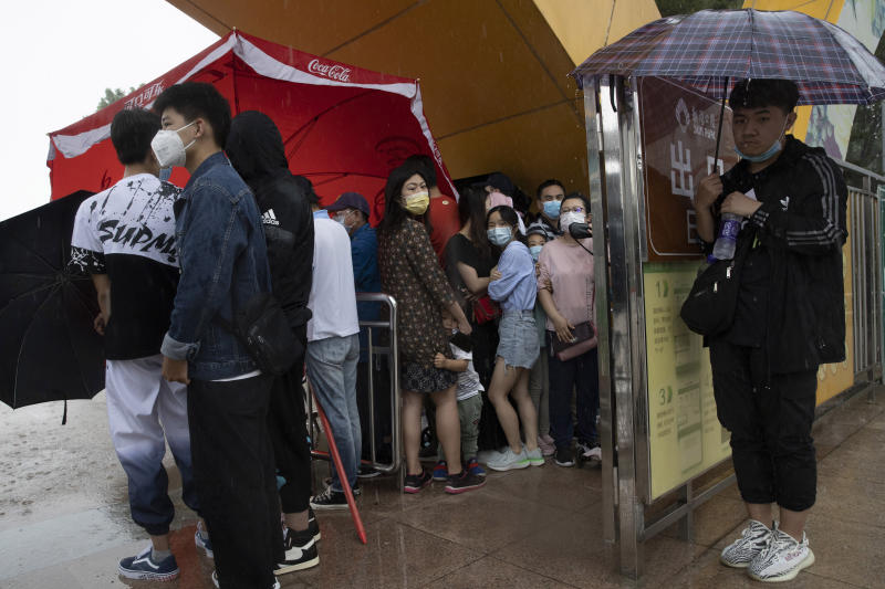 Visitors wearing mask to curb the spread of the coronavirus takes shelter from a sudden rainstorm in Beijing on Saturday, May 23, 2020. New coronavirus cases dropped to zero in China for the first time Saturday but overwhelmed hospitals across Latin America – both in countries lax about lockdowns and those lauded for firm, early confinement. (AP Photo/Ng Han Guan)