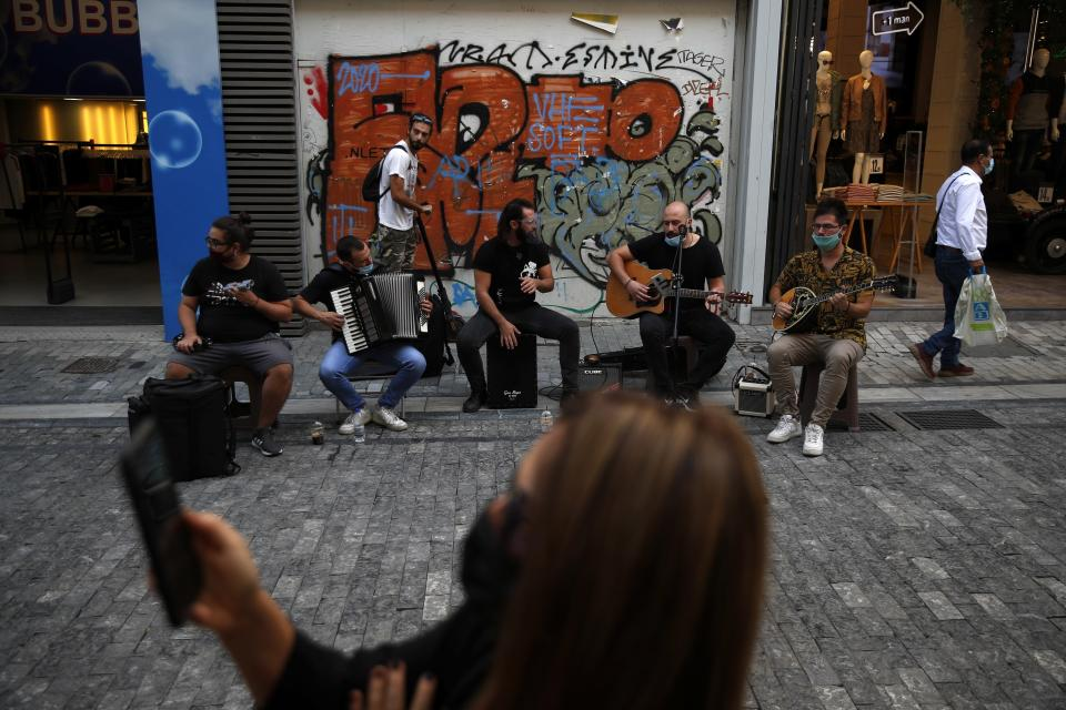 Musicians wearing face masks to prevent the spread of the coronavirus, perform as a woman records a video with her cellphone on Ermou Street, Athens' main shopping area, Monday, Oct. 26, 2020. Greece's government has imposed a nightly curfew in greater Athens and other areas with high infection rates as well as more generalized mask use as the daily number of deaths and infections nationwide has rising in recent weeks. (AP Photo/Thanassis Stavrakis)
